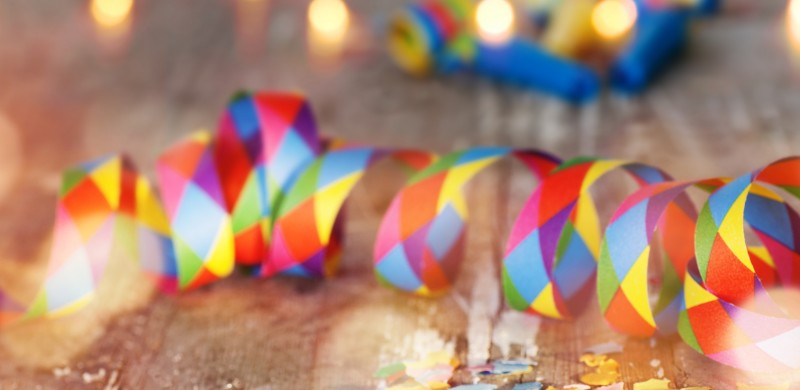 Colorful confetti and air streamer on rustic wooden table with bokeh